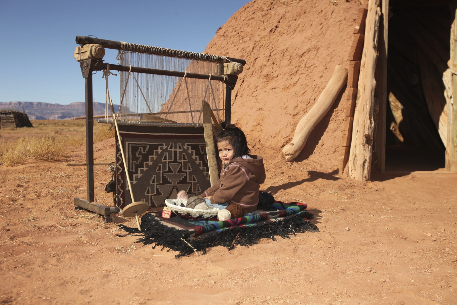 Navajo infant sitting next to a traditional weaving loom