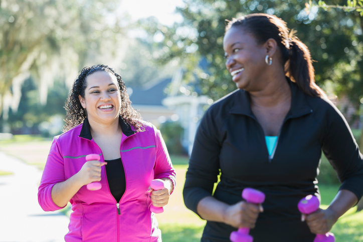 Two women walking for exercise outside on a nice day.