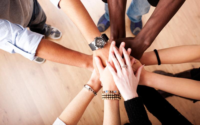 A group of people with their hands together, forming a circle